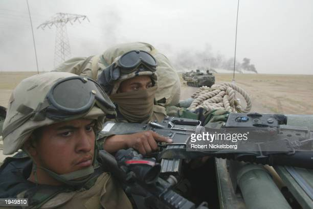 US Marines of the 1st Marine Division watch Iraqi Army tanks burn from their amphibious assault vehicle March 21 2003 25 kilometers south of Basra...