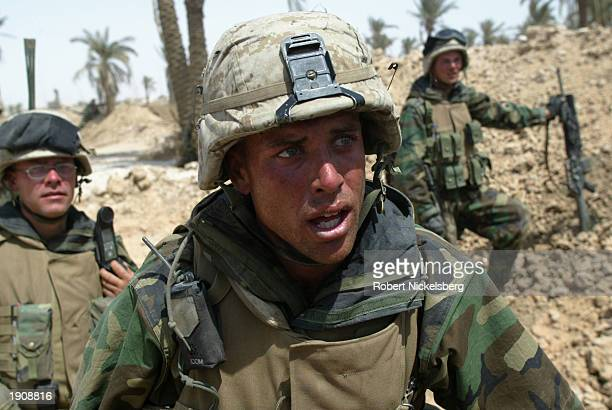 Marines of the 3rd Battalion of the 1st Marine Division react after being ambushed minutes earlier near Al Kut, Iraq, 90 miles south of Baghdad, as...