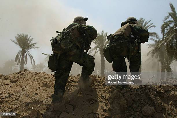 Marines of the 3rd Battalion of the 1st Marine Division secure the entry to Al Kut, 90 miles south of Baghdad, after they were ambushed as they...