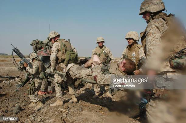 US Marines of the Light Armored Reconnaissance company of the 1st Battalion 3rd Marines care for a wounded soldier after a armored vehicle struck an...