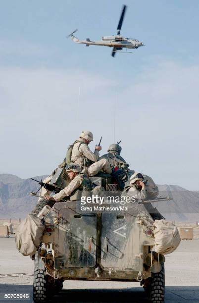 Marines on a Light Armored Vehicle preparing to go on patrol as an AH1W Super Cobra helicopter flies by US Marines are in Afghanistan operating in...
