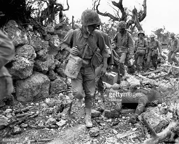Marines pass through a small village where Japanese soldiers lay dead. Okinawa, April 1945.