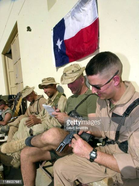US Marines pilots and controllers clean their weapons read write home and generally relax as they sit under the Texas state flag outside their living...