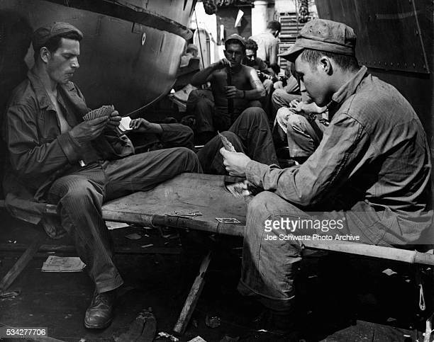 Marines play cards and clean their rifles on a ship bound for Iwo Jima ca 1945 | Location between Hawaii and Iwo Jima