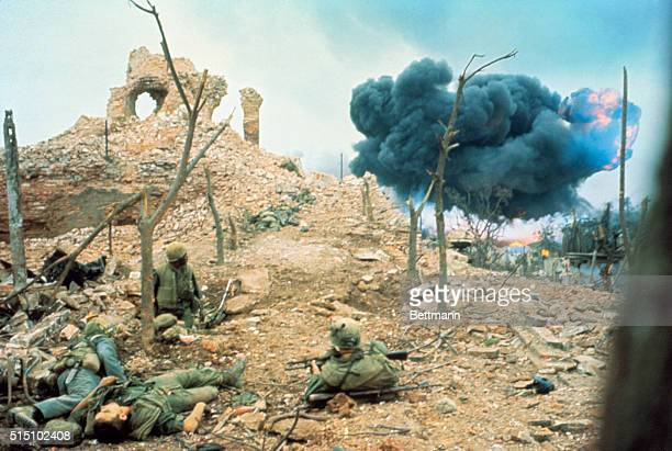 US Marines positioned on brick and stone rubble watch a bomb burst over the hill from a Viet Cong attack