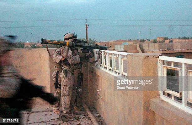 Marines prepare to fire a rocket at a house during a battle with four insurgents as US Marines of the 1st Light Armored Reconnaissance company as...