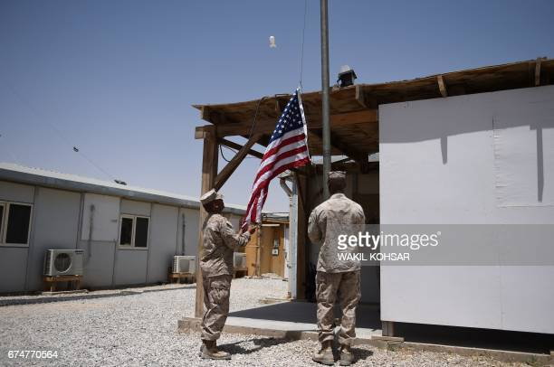 US Marines raise the national flag during a handover ceremony at Leatherneck Camp in Lashkar Gah in the Afghan province of Helmand on April 29 2017...