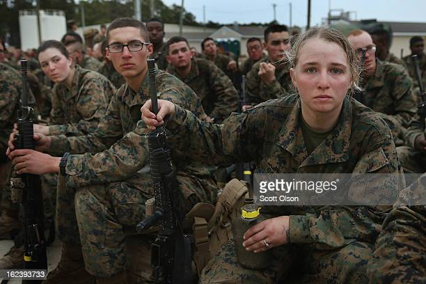 Marines rest following a 10 kilometer training march carrying a 55 pound pack during Marine Combat Training on February 22, 2013 at Camp Lejeune,...