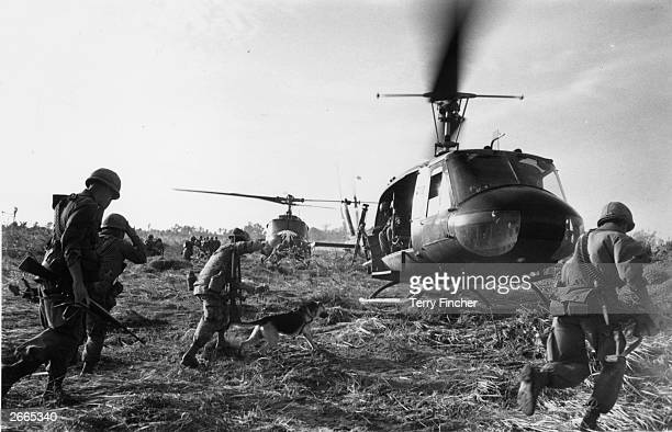 US marines running towards a Bell Huey helicopter and crew in the Tay Ninh area of Vietnam