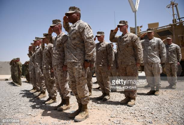 US Marines salute during a handover ceremony at Leatherneck Camp in Lashkar Gah in the Afghan province of Helmand on April 29 2017 US Marines...