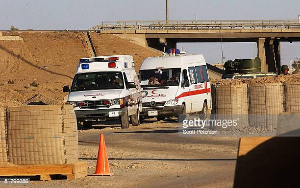 Marines search a convoy of vehicles and staff of the Iraqi Red Crescent at the first checkpoint into Fallujah for weapons and nonaccredited staff on...