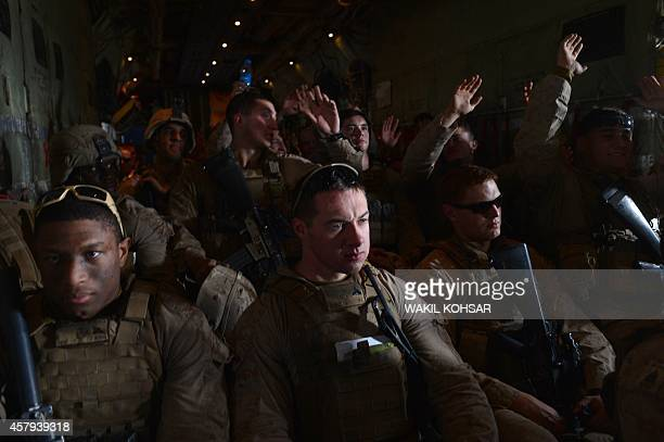 US Marines sitting inside the cargo hold of a C130J Super Hercules transport aircraft headed to Kandahar gesture as British and US forces withdraw...