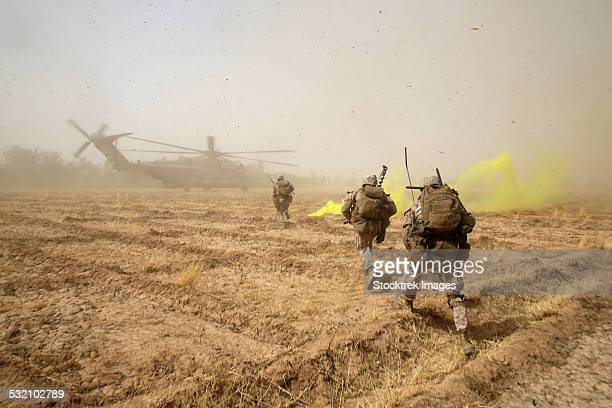 u.s. marines sprint across a field to load onto a ch-53e super stallion. - afghanistan war stock photos and pictures