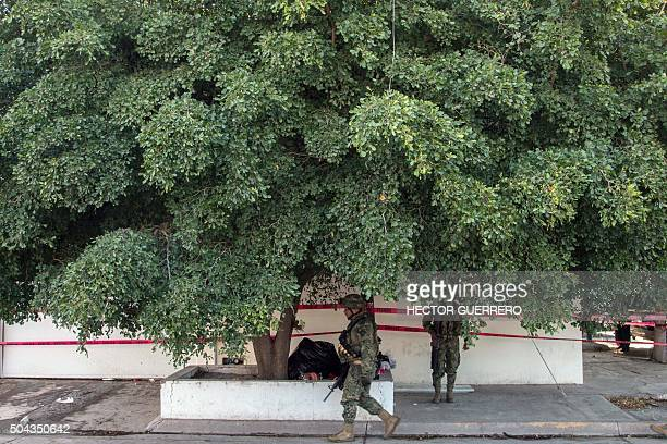 TOPSHOT Marines stand guard outside the house where five gang suspects were killed in the military operation which resulted in the recapture of...
