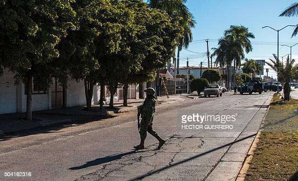 Marines stands guard on January 9 2016 on the street in front of the house where five gang suspects were killed in the military operation which...