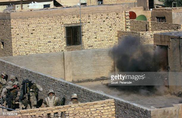 Marines take cover as they blast open a door with explosives as US Marines of the 1st Light Armored Reconnaissance company as part of 1st Battalion...