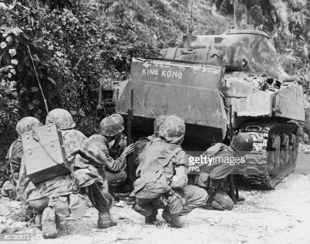 Marines take cover behind a flame-throwing Sherman tank, nicknamed 'King Kong', at the extreme northern end of Saipan Island during the Battle of...