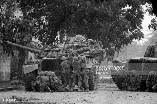 US Marines take cover behind a tank in Hue 2/1 after Viet Cong terrorists snipers opened fire on them The Marines along with the South Vietnamese...