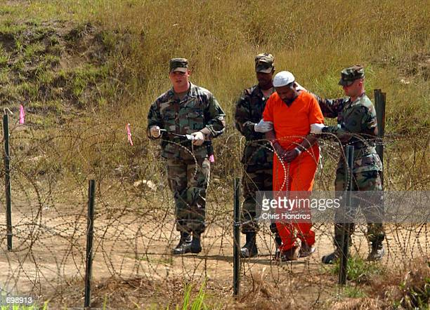 Marines transport a detainee in Camp XRay February 6 2002 in Guantanamo Bay Cuba Many of the 156 AlQaeda or Taliban detainees are transported around...