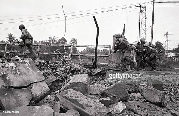US marines try to avoid gunfire as they cross a bridge in Hue South Vietnam during the Vietnam War