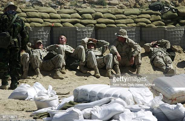 Marines try to shield their eyes from the harsh sun as they rest after spending hours building bunkers at Al Jaber Air Base in the Kuwaiti desert...