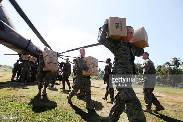 Marines unload boxes of MRE's as a Navy helicopter delivers the food for victims of the massive earthquake on January 23, 2010 in Leogan, Haiti....
