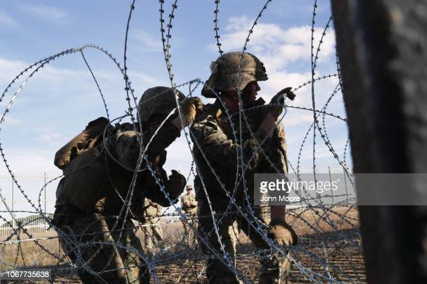 S Marines untangle each other from razor wire while installing it along the USMexico border fence on December 2 2018 as seen from Tijuana Mexico...