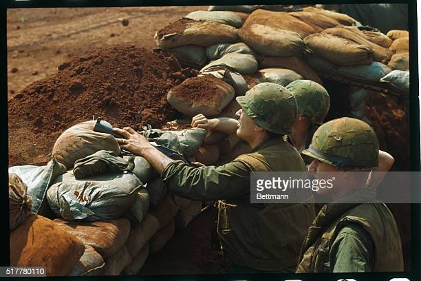 US Marines uses binoculars to watch the effect of American jet bombing North Vietnamese zigzag trenches just outside the defensive perimeter of this...