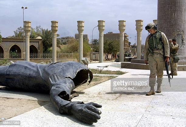US Marines walk pass a dismounted statue of Saddam Hussein on Baghdad's alFardous square 10 April 2003 As the regime of Saddam Hussein collapsed...