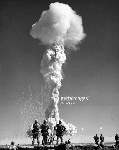 Marines watch an atomic cloud surge upward during one of the exercises at the Atomic Energy Commission's Proving Ground in which Army and Marine...