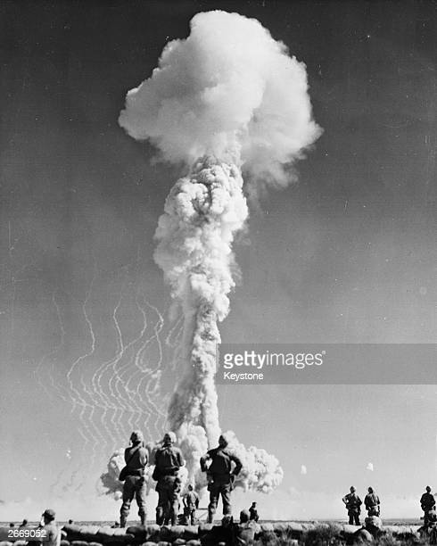 US marines watch the mushroom cloud from an atomic explosion rise above the Yucca flats Nevada during a US nuclear weapons test
