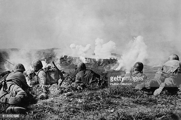 Marines watch the results of their phosphorous shell attack on their campaign in Okinawa.