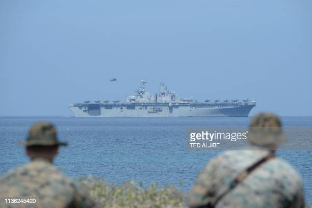 US Marines watch the US navy multipurpose amphibious assault ship 'USS Wasp' with F35 lightning fighter jets on the deck during the amphibious...