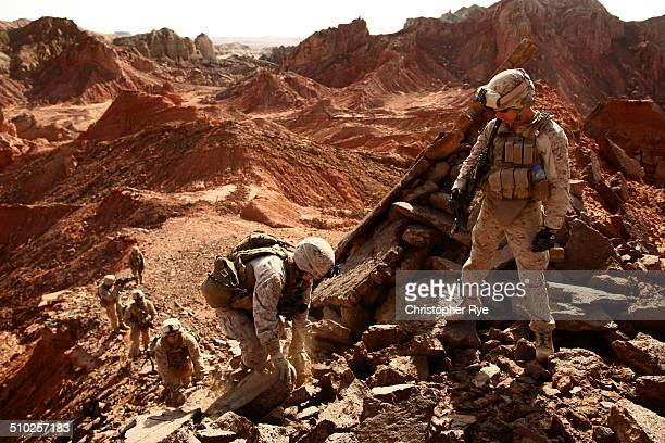 US Marines with 2nd Marine Division and 1st Light Armored Reconnaissance Battalion climb through rocky terrain of a mountain chain in Helmand...