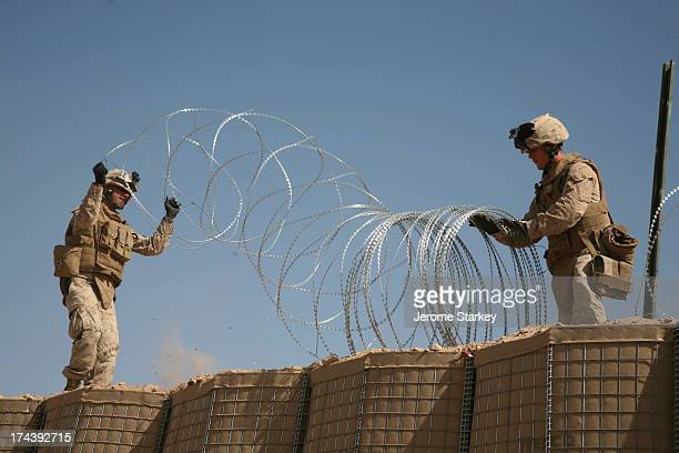 Marines with NATO forces put barbed wires on top of the protective walls around a newly setup joint Afghan National Army and NATO military base in...