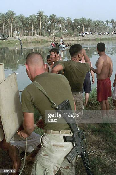 S Marines with the help of Iraqis work to secure the wreckage of a CH46 Sea Knight helicopter that crashed May 19 2003 in the Shat alHillah Canal...