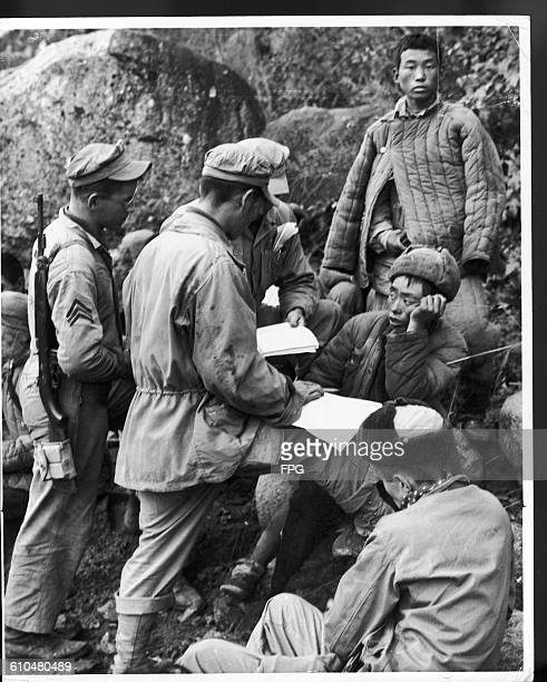 Marines with their Chinese prisoners at Chosin Reservoir in Changjin County, North Korea, during the Korean War, 1950. Here Marine Technical Sergeant...