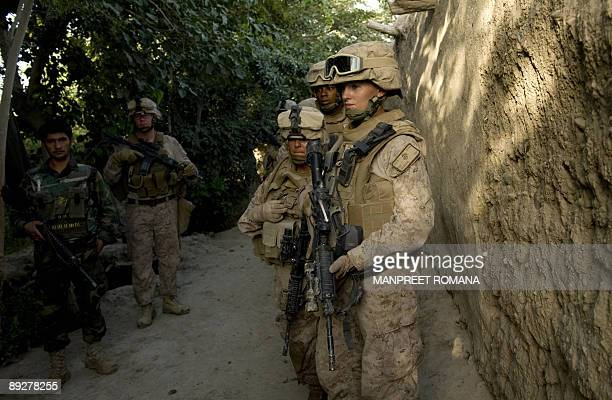 US Marines women search team of 2nd Marine Expeditionary Brigade wait to enter a compound as US Marines help Afghan National Army search compounds...