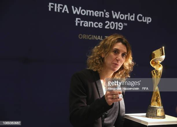 Marinette Pichon of France poes next to the winners trophy of the FIFA Women's World Cup 2019 France is displayed at La Seine Musicale on December 7...