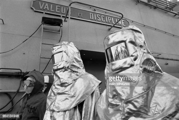 Marins en tenue de protection sur la Jeanne d'Arc bateau école de la marine française Brest le 8 décembre 1983 France