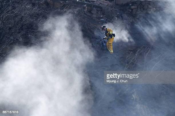 Marinwood firefighter Brandon Selvitella knocks down smoldering embers on a hillside off Wentworth Street in SunlandTujunga on December 6 2017 in...