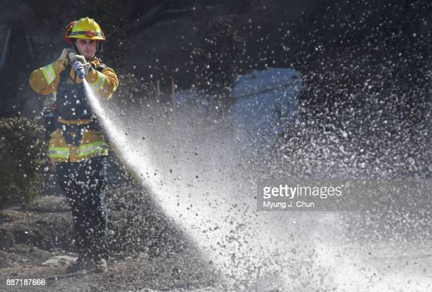 Marinwood firefighter Dan Rotwein hoses down hotspots on Wentworth Street in SunlandTujunga where stacks of tires were set ablaze during the Creek...