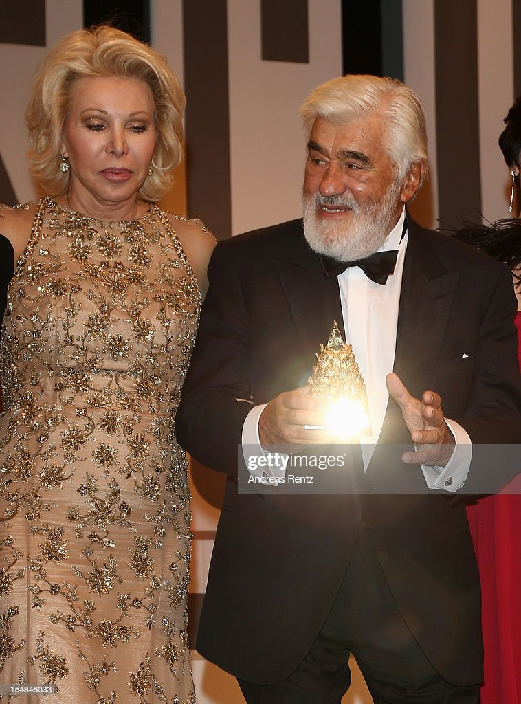 Mario Adorf holds up his award as Ute Ohoven looks on during the 21st UNESCO Charity Gala 2012 on October 27, 2012 in Dusseldorf, Germany.