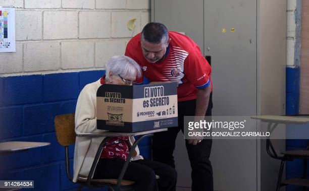 Mario Alfaro assists his 85yearold mother Maruja to cast her vote at a polling station set up at Carlos Sanabria elementary school in San Jose during...