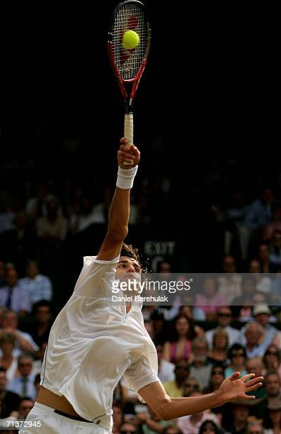Mario Ancic of Croatia serves to Roger Federer of Switzerland during day nine of the Wimbledon Lawn Tennis Championships at the All England Lawn...