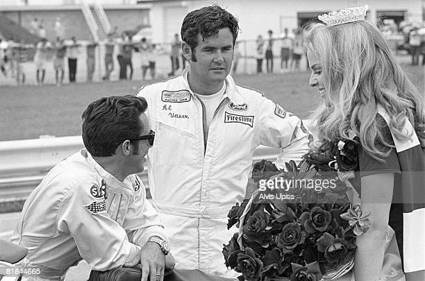 Mario Andretti and Al Unser chat with the race queen before the start of the USAC INDY 150 Champ Car Race held on the road course at Indianapolis...