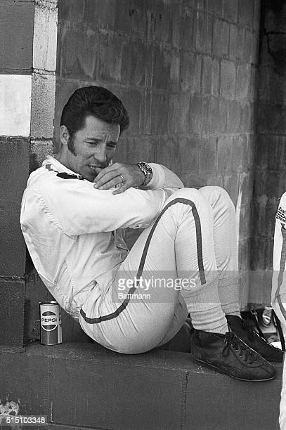 Mario Andretti from Nazareth, Pennsylvania, bites on his thumb as his crew works on his Ferrari 512/s in the pitt. Andretti will drive one of the 70...