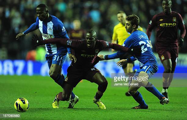 Mario Baloteli of Manchester City battles with Maynor Figueroa and Adrian Lopez of Wigan during the Barclays Premier League match between Wigan...