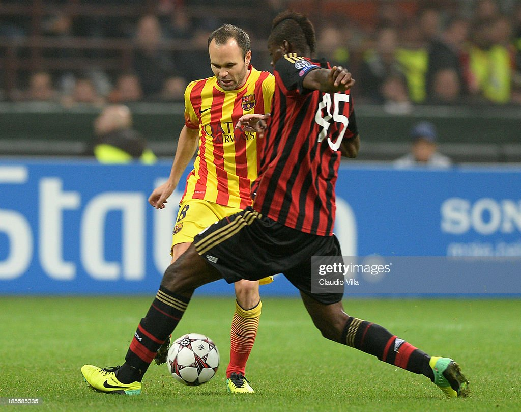 Mario Balotelli of AC Milan and Andres Iniesta of FC Barcelona (L) compete for the ball during the UEFA Champions League Group H match between AC Milan and Barcelona at Stadio Giuseppe Meazza on October 22, 2013 in Milan, Italy.