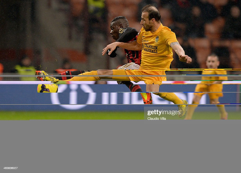 Mario Balotelli of AC Milan (L) and Vangelis Moras of Hellas Verona compete for the ball during the Serie A match between AC Milan and Hellas Verona FC at San Siro Stadium on January 19, 2014 in Milan, Italy.